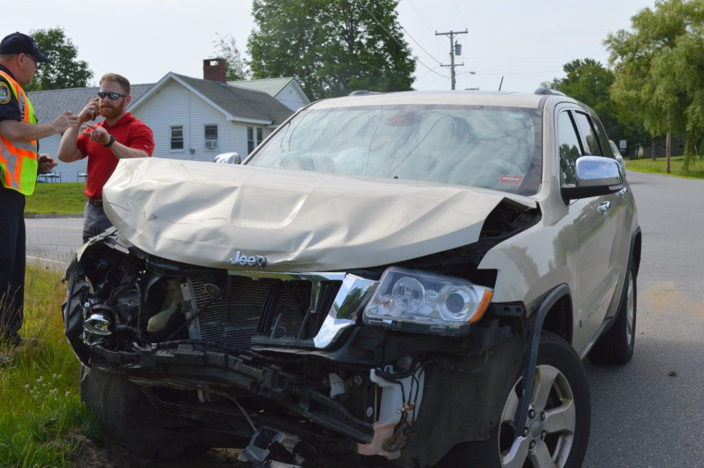 Jay Police Officer David Morin, left, speaks with Russell Bailey, 31, of Farmington on Tuesday morning after his Jeep Cherokee and a Chevrolet Malibu driven by Scott Moore, 50, of Auburn, collided at Routes 133 and 156 in Jay.