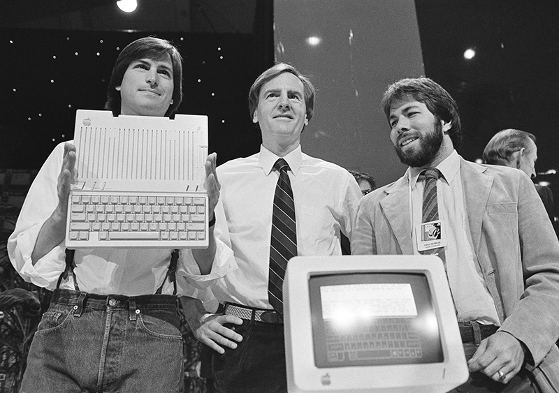 FILE - In this April 24, 1984 file photo, Steve Jobs, left, chairman of Apple Computers, John Sculley, center, president and CEO, and Steve Wozniak, co-founder of Apple, unveil the new Apple IIc computer in San Francisco, Calif.  Apple has become the world's first company to be valued at $1 trillion, the financial fruit of tasteful technology that has redefined society since two mavericks named Steve started the company 42 years ago.  Associated Press/Sal Veder