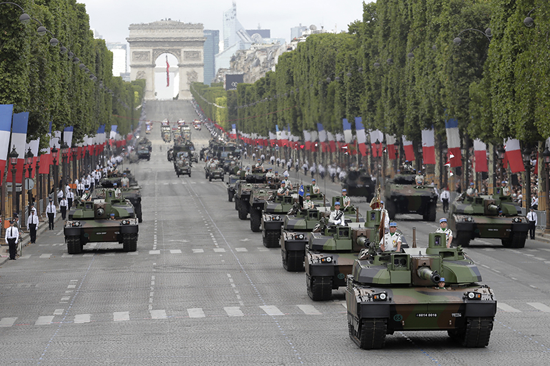 "Tanks drive down the Champs Elysees avenue during the Bastille Day parade in Paris in 2017. Trump attended the parade and said later  ""We're going to have to try and top it."""