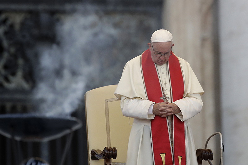 Pope Francis prays during an audience in St. Peter's square at the Vatican on Tuesday.