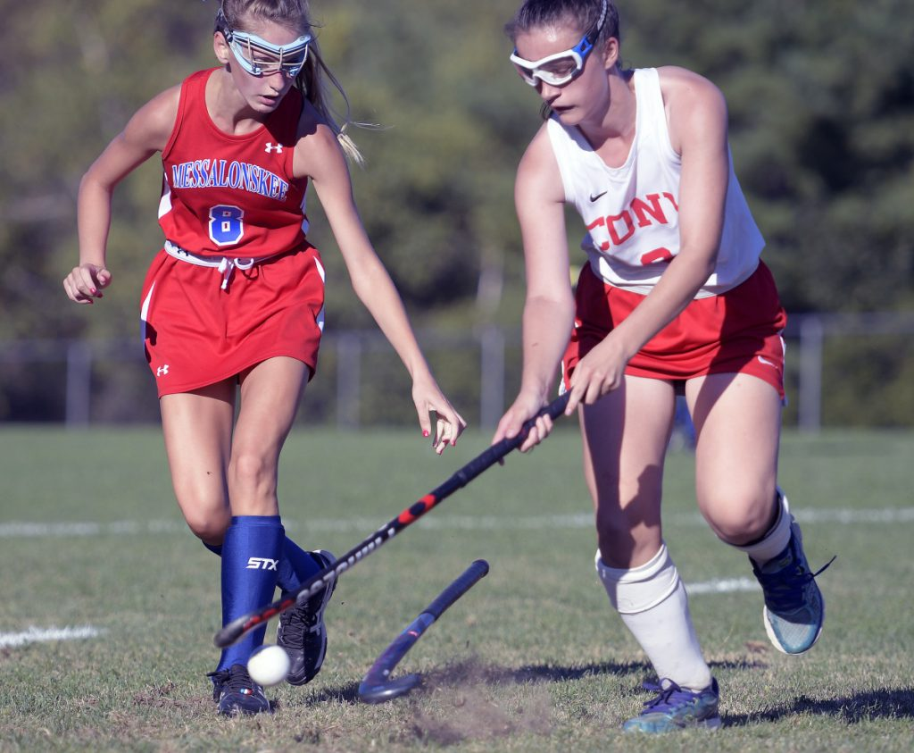 Cony's Anna Stolt, right, knocks the stick away from Messalonskee's Megan Quirion during a field hockey game Thursday in Augusta.