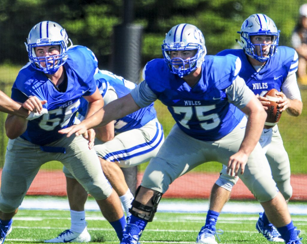 Colby College offensive linemen Ty Mahar, left, and Brandon Troisi block for quarterback Jack O'Brien during a game against Trinity earlier this in Waterville.