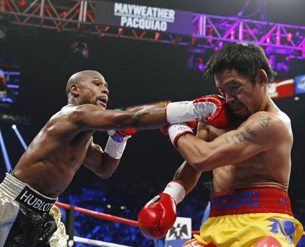 Floyd Mayweather Jr., left, connects with a right to the head of Manny Pacquiao during their welterweight title fight in May 2015 in Las Vegas. Mayweather Jr. says he's coming out of retirement again to fight Pacquiao for a second time in December. Mayweather posted a video on Instagram early Saturday that showed Pacquiao and him together, reportedly in Japan, jawing at each other over a possible second fight.