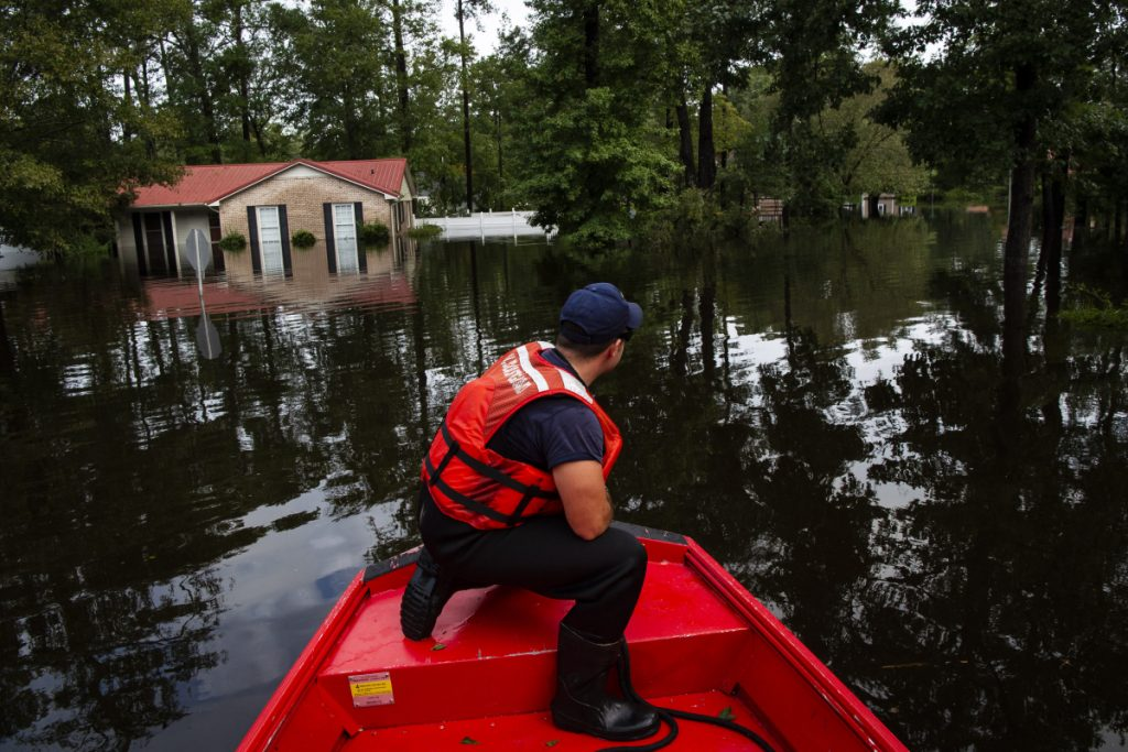 Boatswain's Mate Dimitri Georgoulopoulos looks out as members of a punt team with the United States Coast Guard preform searches through floodwater in the MayFair neighborhood of Lumberton, North Carolina, in the aftermath of Hurricane Florence on Monday.