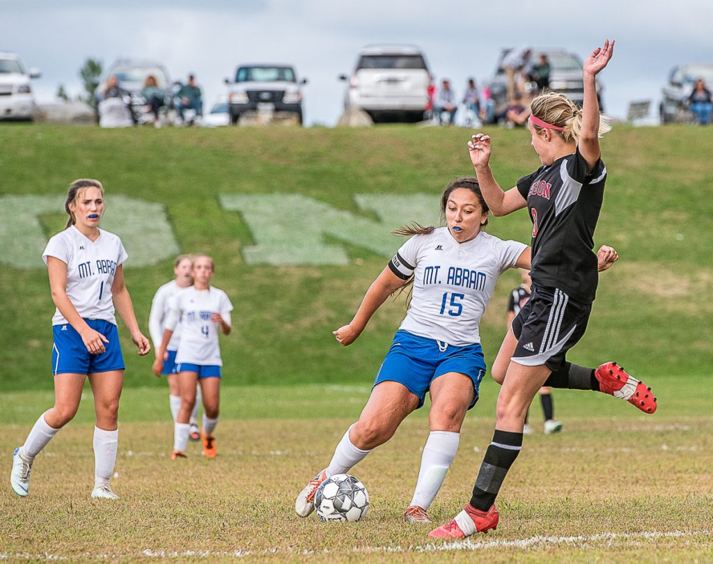 Sun Journal photo by Andree Kehn   Mt Abram's Summer Ross, left, tries to maneuver around Lisbon defender Siara Martin during a game Wednesday afternoon.
