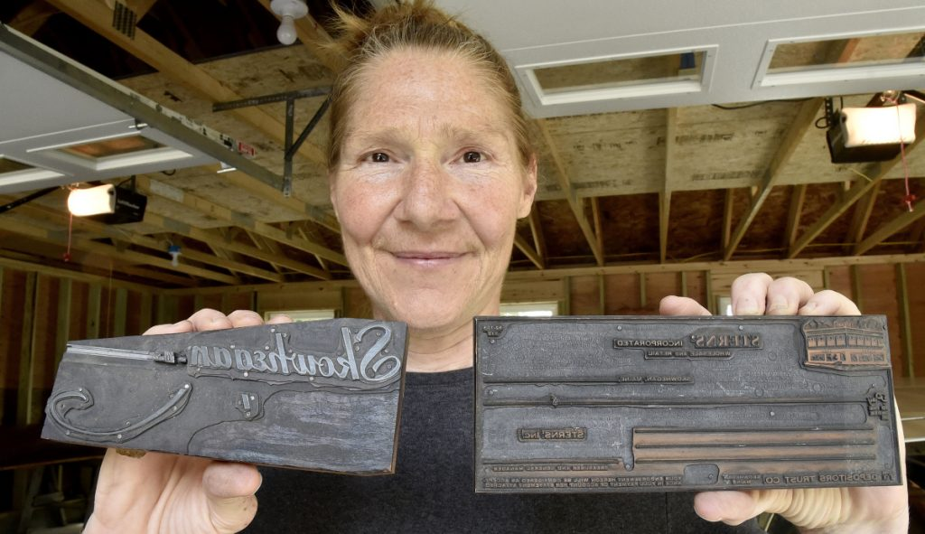 "Kim Wilson on Tuesday holds metal plates used in printing newspapers that are part of a collection of hundreds of editions of Somerset County newspapers dating back to the mid-1800s that will become part of an extensive collection in Skowhegan. On the block at left, ""Skowhegan, Me."" is engraved backward."
