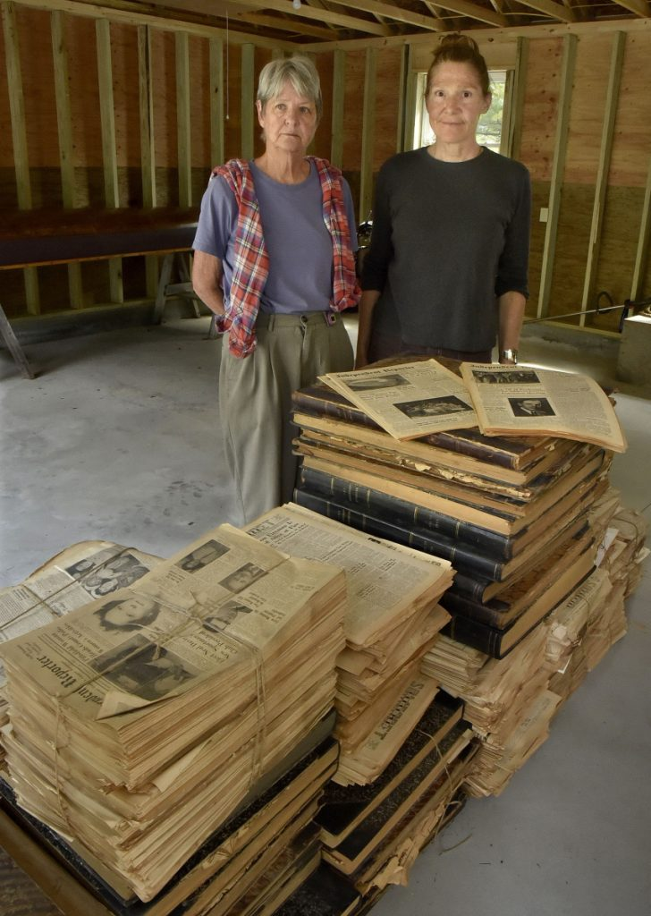Patricia Horine, left, and Kim Wilson display on Tuesday some of the hundreds of editions of Somerset County newspapers dating back to the mid-1800s that will become part of an extensive collection in Skowhegan.