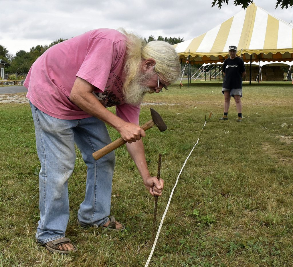 Ernie Glabau, a vendor and agriculture coordinator for the Common Ground Country Fair, stakes borders on Tuesday for a tent that will include his Entwood Bonsai tree booth while getting ready for the three-day fair in Unity that begins Friday.