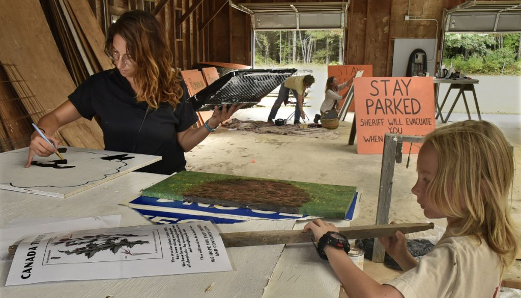 Jennifer Sansosti and Luca McCune work on signs with others in preparation for the Maine Organic Farmers and Gardeners Association annual Common Ground Country Fair in Unity on Tuesday. The three-day fair starts Friday.