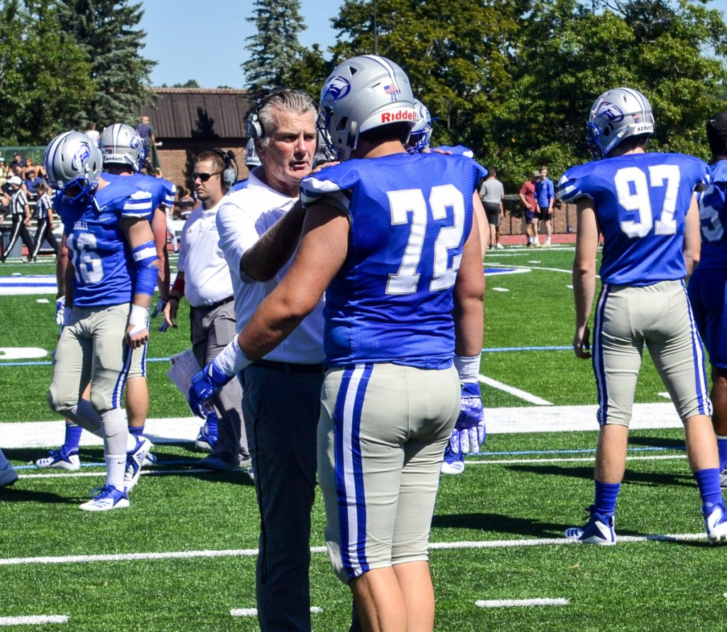 New Colby College head football coach Jack Cosgrove talks with a player before a game against Trinity on Saturday in Waterville.