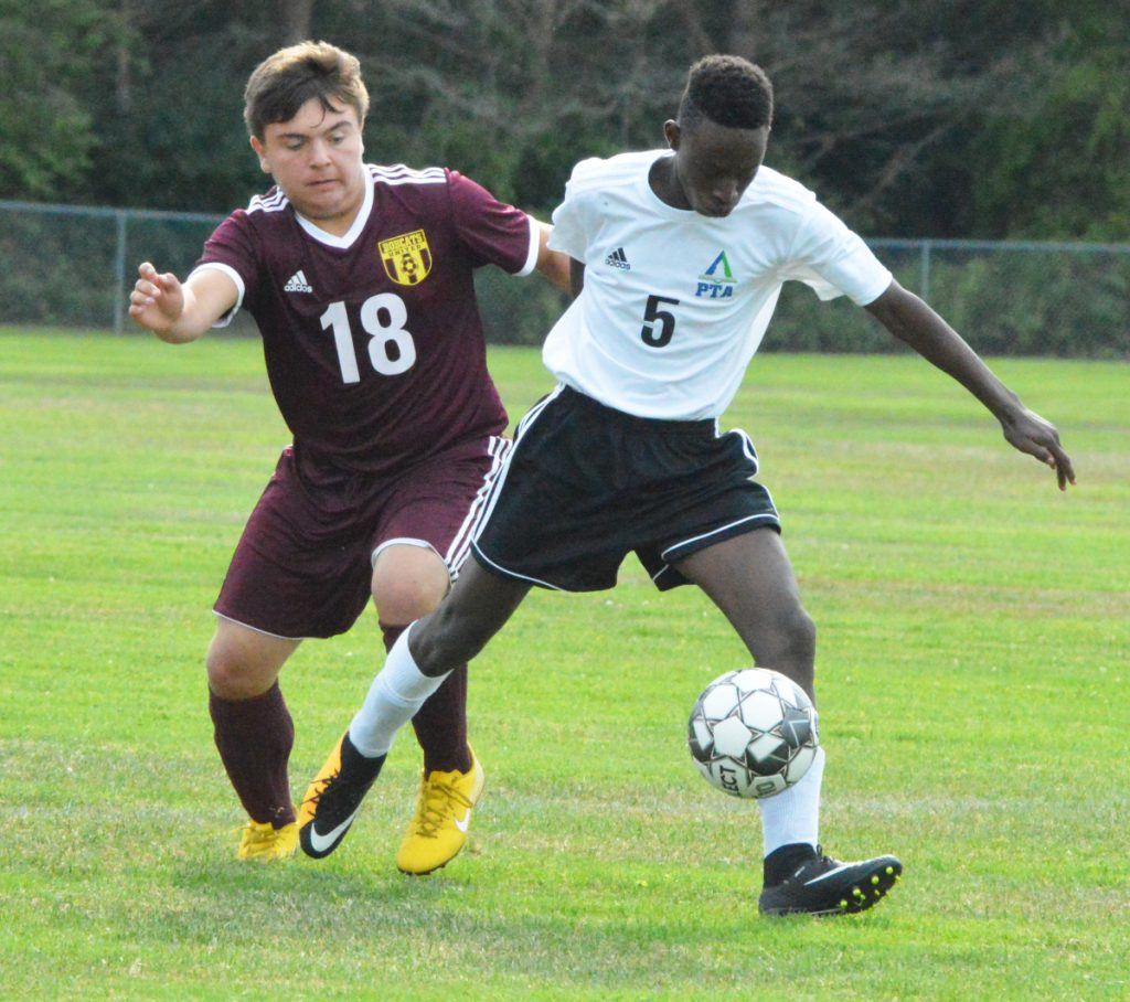 Richmond's Derek Barrett (18) battles with Pine Tree Academy's Nshimiye Gasuminari (5) during Thursday's Class D South soccer game in Richmond.