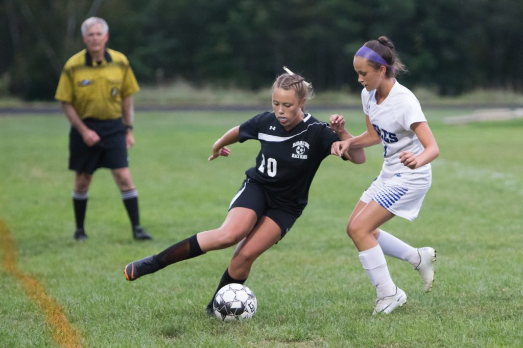 Maranacook's Ella Delisle takes control of the ball while Erskine's Mackenzie Roderick defends her Thursday in Readfield.