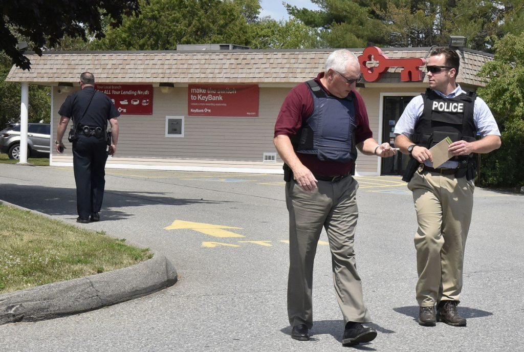 Waterville police Chief Joe Massey, left, and Sgt. David Caron confer July 10 outside the KeyBank branch on Kennedy Memorial Drive in Waterville while investigating a robbery there.