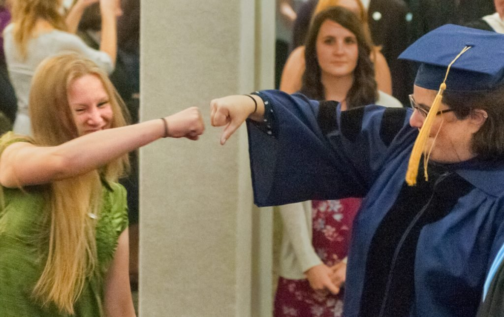 Rising Scholar Jacinta Hunt, left, and Lorien Lake-Corral, the professor who nominated her, bump fists Friday as they part company during the entrance processional at the annual University of Maine at Augusta convocation at the Augusta Civic Center.