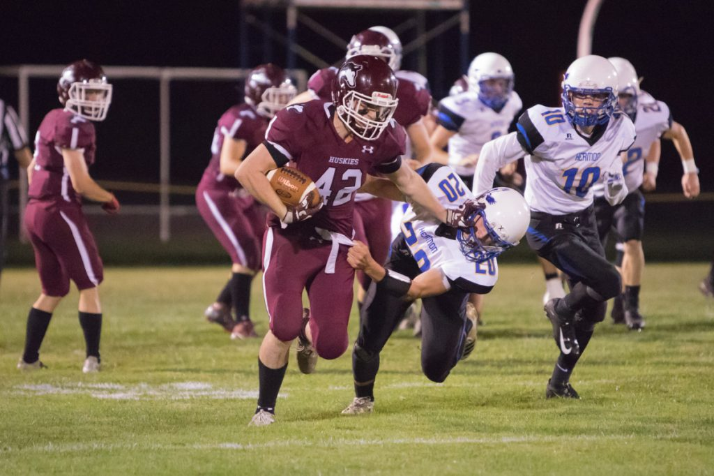 Maine Central Institute ball carrier Tucker Sharples tries to shake off Hermon defender Garrett Trask during a Class C North game Friday night in Pittsfield.