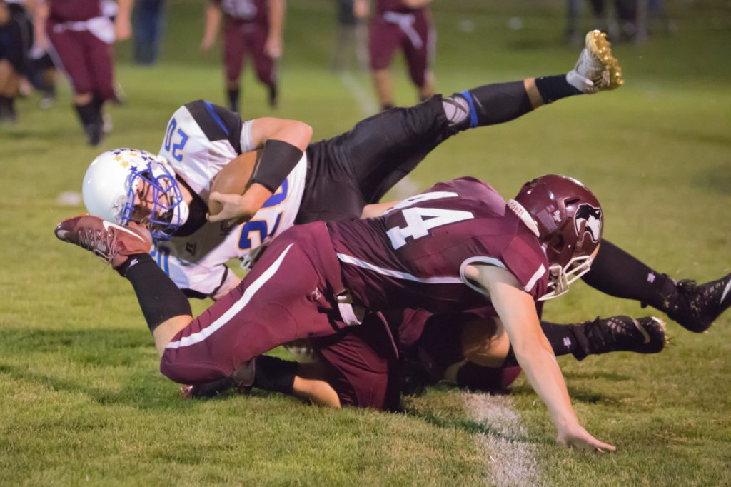 Hermon's Garrett Trask gets wrapped up by Maine Central Institute defender Kempton Roy during a Class C North game Friday night in Pittsfield.