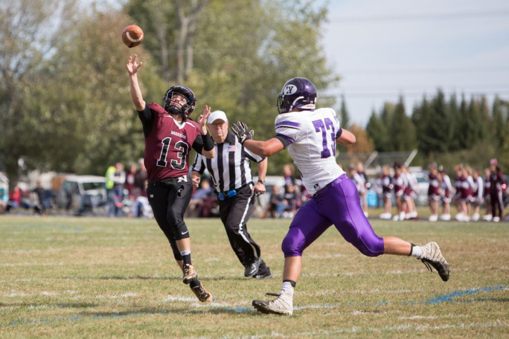Nokomis quarterback Andrew Haining gets off a pass as Waterville defender Jack Lloyd pursues during a Class C North game Saturday in Newport.