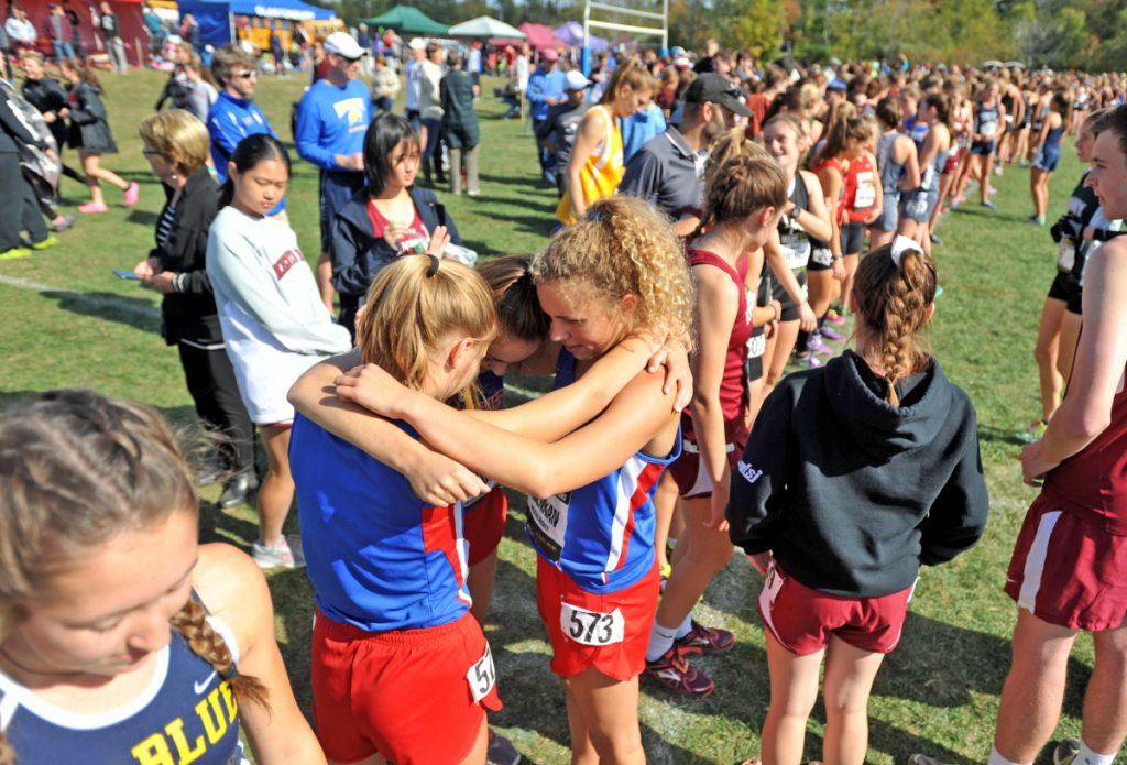 Messalonskee's Alexa Brennan, center, Charlotte Wentworth, left center, and Peyton Arbor, left, embrace at the starting line before competing in the Festival of Champions last Otober in Belfast.