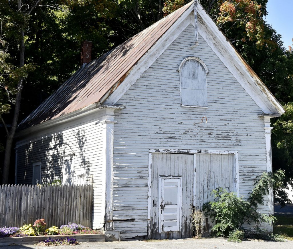 Oakland town councilors decided Monday to accept Norman Vigue's bid to buy the former school building at 97 Church St. that sits next to his residence and business.
