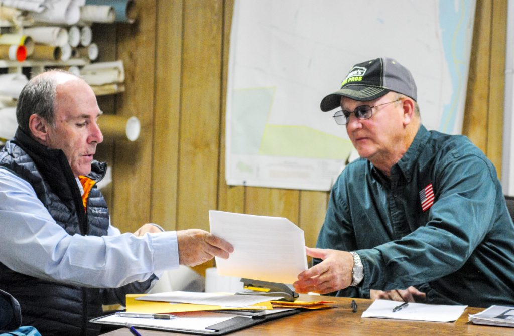 Mark McCluskey, of A.E. Hodson Consulting Engineers, passes along one of the bids for construction of a Farmingdale fire station to Selectman Wayne Kilgore on Tuesday in the Farmingdale Town Office.