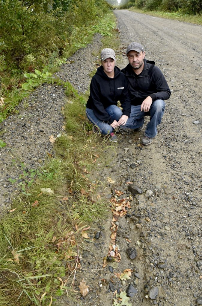 Albion residents Leanne York and Robert Brown crouch next to the rutted Marks Road on Tuesday to show that the road's shoulder is considerably higher than the roadway and prevents water from running off the road surface. Brown said he has complained to town officials about it since 2016.