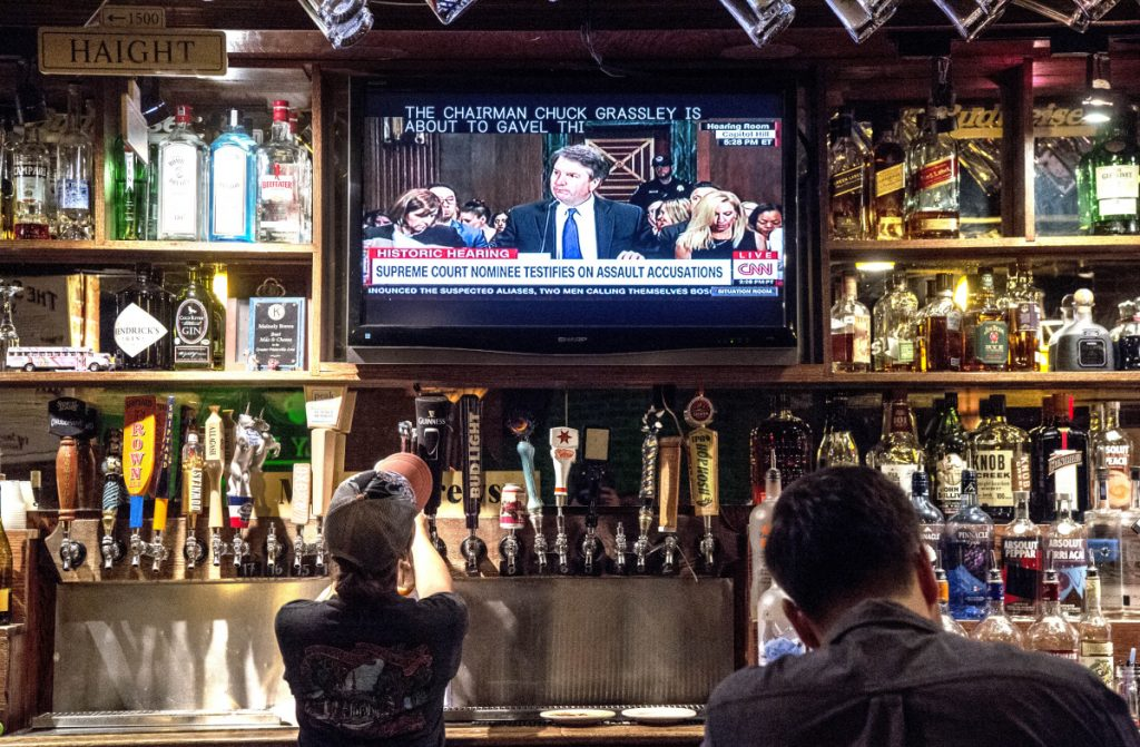 People watch the Brett Kavanaugh Judiciary Committee hearing on television at Mainely Brews on Thursday.