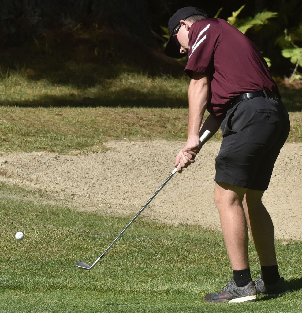 Staff photo by David Leaming   Monmouth's Trevor Flanagan chips a shot during the Mountain Valley Conference championships Thursday at Natanis Golf Course in Vassalboro.
