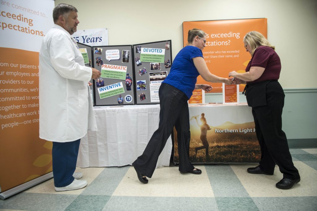 Susan Irving, far right, a dietary aide at Inland Hospital, receives information on the impending name change from communications specialist Kathy Jason as Rick Barry, a registered nurse and vice president of patient care services, looks on on Friday.
