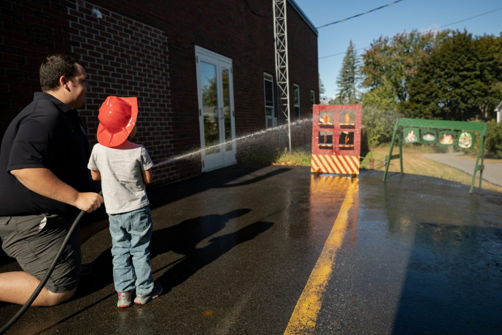Winslow on-call firefighter Joel Cloutier, left, assists Jamison Emery, 3 of Winslow, in an exercise that teaches children to aim a water hose to put a fire out. Cloutier, who has worked with the Winslow Fire Department for one week, was taking part in an open house Saturday morning at the Winslow Fire Department.