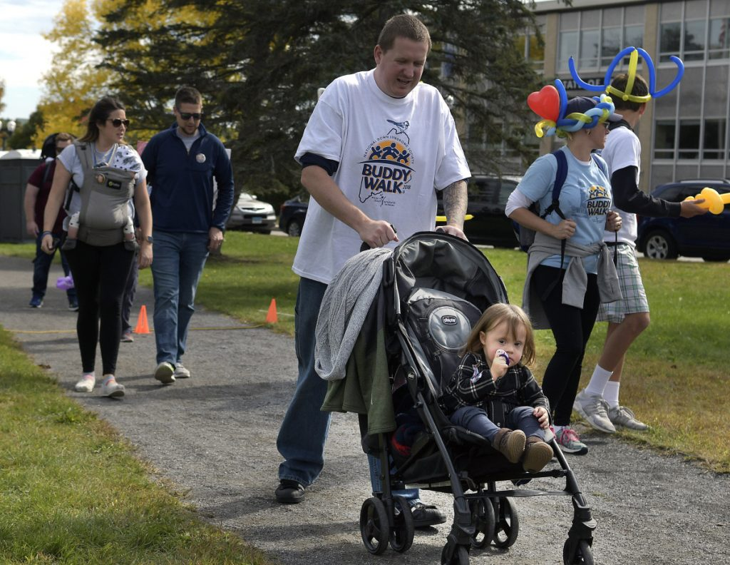 Luna Sorenson, 1, of Rumford, accompanies her father, Tom, on Sunday on the Augusta Buddy Walk, presented by the Maine Down Syndrome Network.