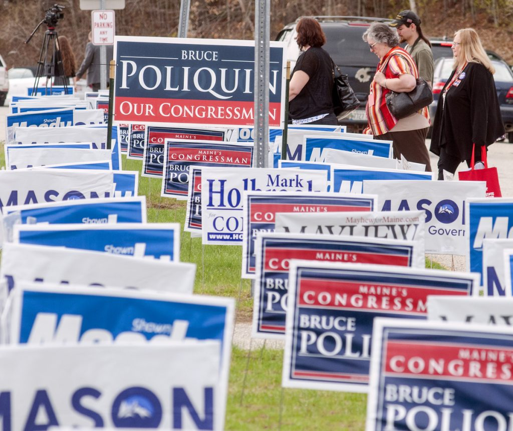 During lunch break Friday, people walk past signs outside the Augusta Civic Center during the Maine Republican Party convention. Staff photo by Joe Phelan/Staff Photographer