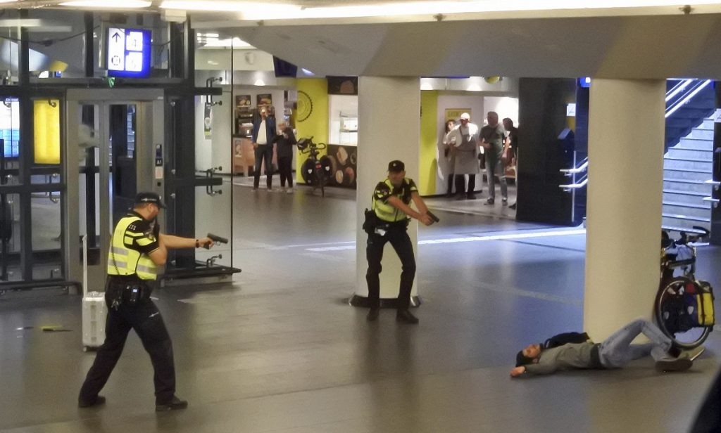 Dutch police point their guns at a wounded 19-year-old Afghan suspect who was shot by officers after allegedly stabbing two Americans in the central railway station in Amsterdam on Friday. The Americans are recovering in a hospital.