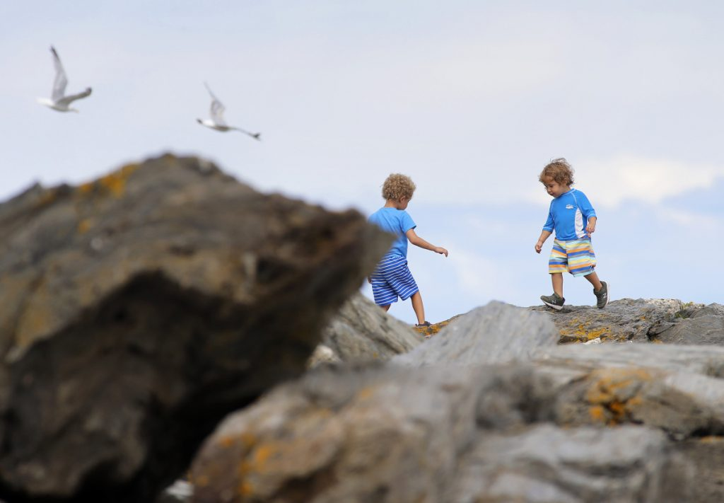 Brothers Rylan, left, and Macen of New Gloucester play on the rocks at Two Lights State Park in Cape Elizabeth on Thursday.