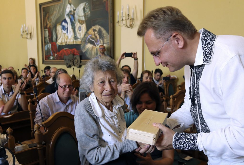 Lviv Mayor Andriy Sadoviy, right, presents a glass copy of an old metal synagogue key to Yanina Hescheles, Polish writer and a Nazi concentration camp survivor, at a ceremony Sunday commemorating the 75th anniversary of the annihilation of the city's Jewish population by Nazi Germany in Lviv, Ukraine.