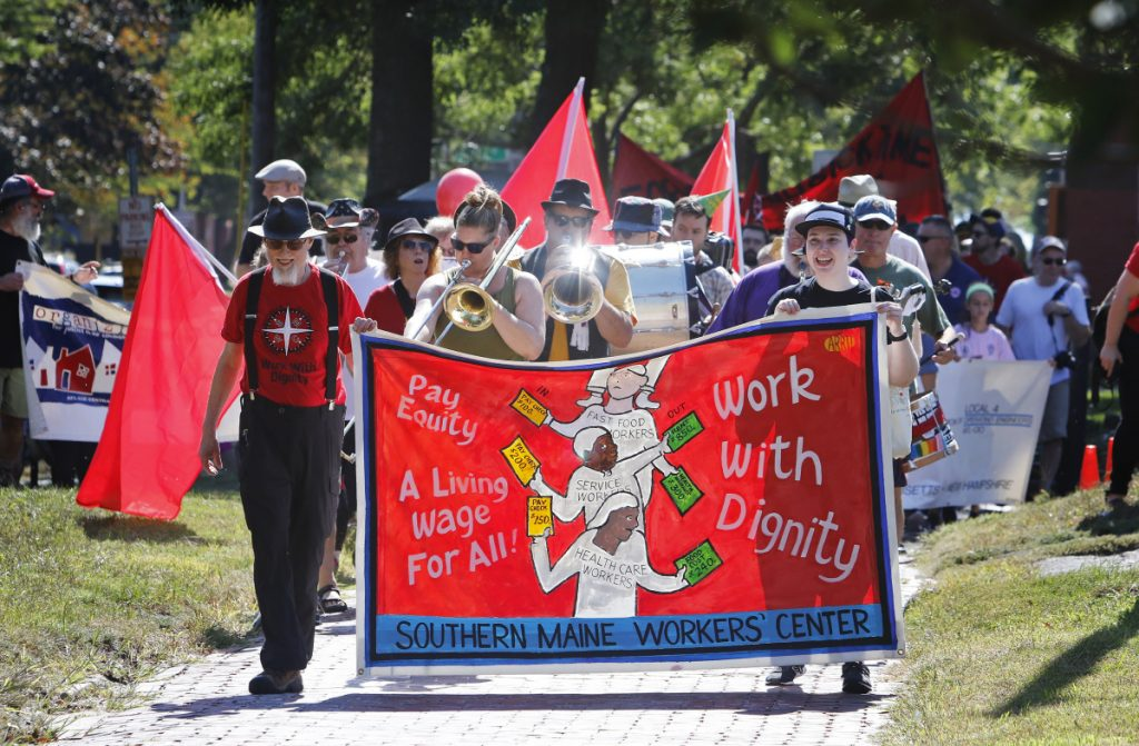 Participants in the Southern Maine Labor Council AFL-CIO's march proceed Monday along State Street in Portland.