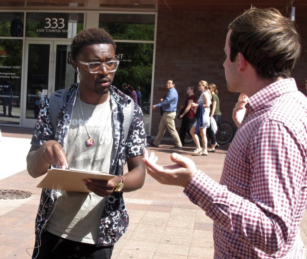 In this Thursday, Aug. 30, 2018 photo, University of Wisconsin freshman Kellen Sharp, left, gets information about registering to vote from NextGen America worker Sean Manning, right, in Madison, Wis. Sharp says he's excited to vote. He and others at the Madison event think young people are more energized than ever. (AP Photo/Scott Bauer)