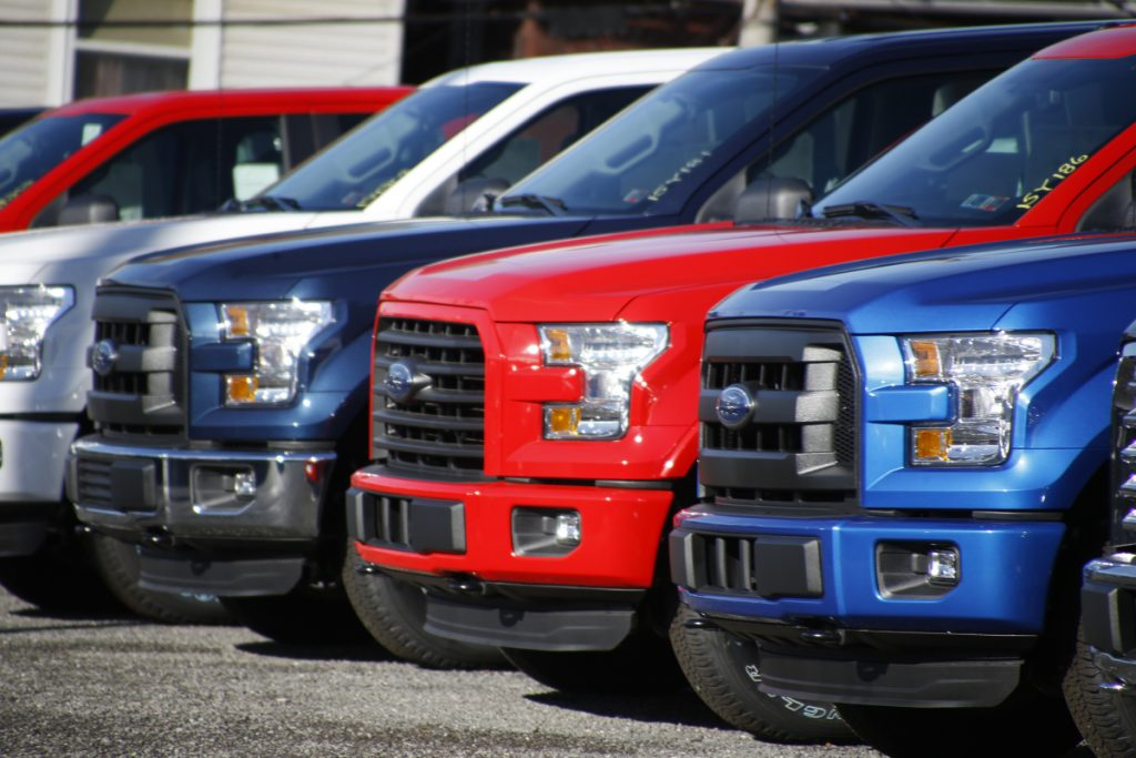 FILE- In this Nov. 19, 2015, file photo a row of 2015 Ford F-150 pickup trucks are parked on the sales lot at Butler County Ford in Butler, Pa. Under pressure from U.S. safety regulators, Ford is recalling about 2 million F-150 pickups in North America because the seat belts can cause fires. The recall covers certain trucks from the 2015 through 2018 model years. Associated Press/Keith Srakocic
