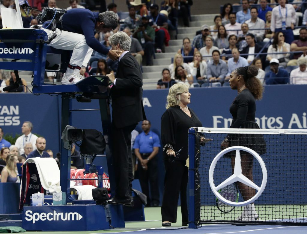 Chair umpire Carlos Ramos, left, talks with referee Brian Earley as Serena Williams talks with Donna Kelso during the women's final of the U.S. Open against Naomi Osaka on Saturday in New York.