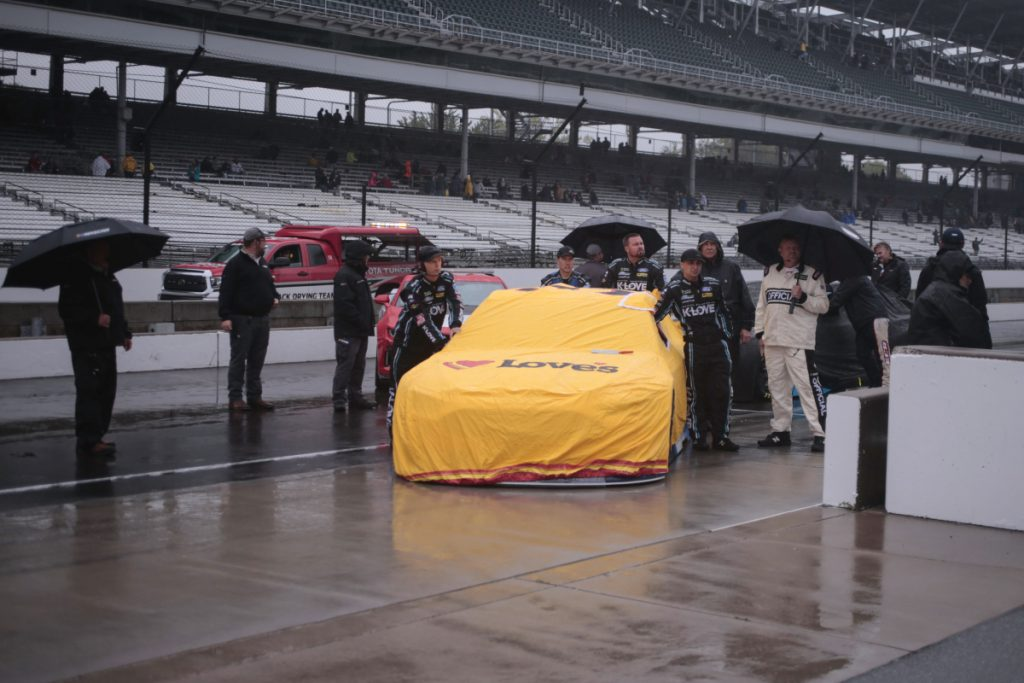 The team of NASCAR Cup Series driver Michael McDowell push his car to the garage area during a rain delay before the Brickyard 400 at Indianapolis Motor Speedway in Indianapolis, Sunday. The race was postponed until Monday.