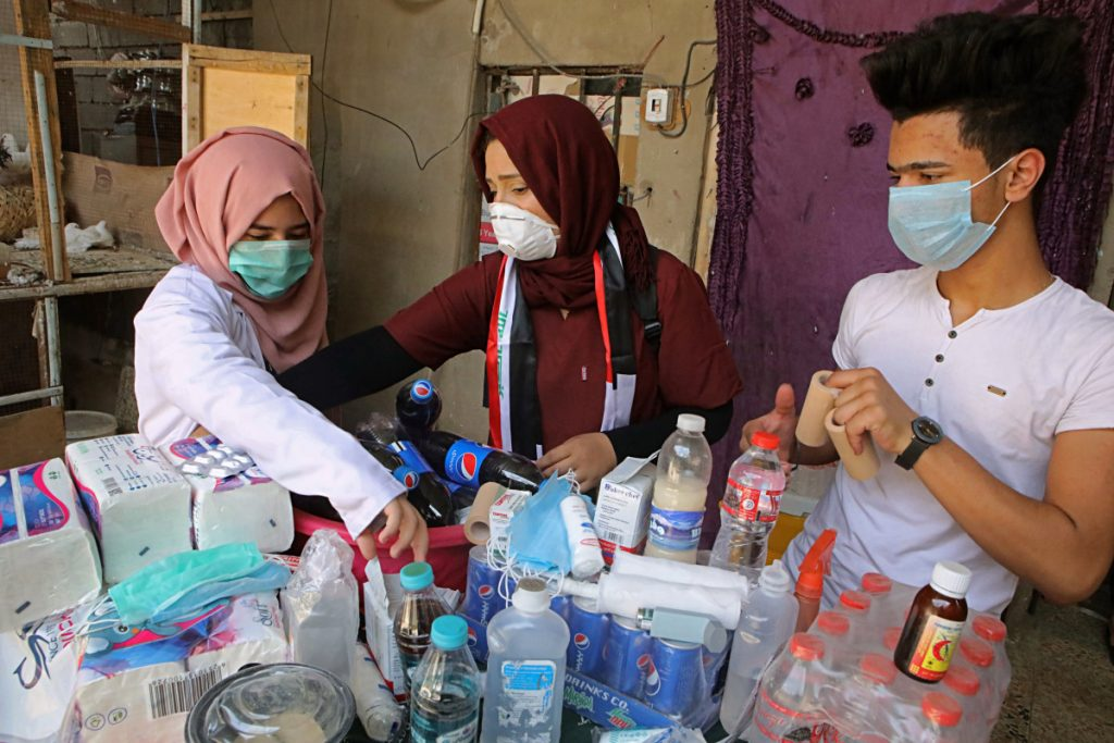 Duhaa Mayaa, center, and her two children prepare first aid supplies for injured protesters in their home in Basra, Iraq. With brackish water pouring from the taps, failing city services and soaring unemployment, the southern Iraqi city has seen weeks of violent protests in the streets.