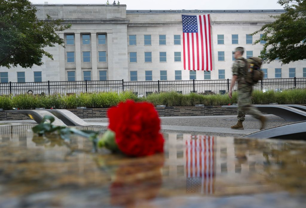 A member of the military walks the grounds of the National 9/11 Pentagon Memorial before the start of the September 11th Pentagon Memorial Observance at the Pentagon.