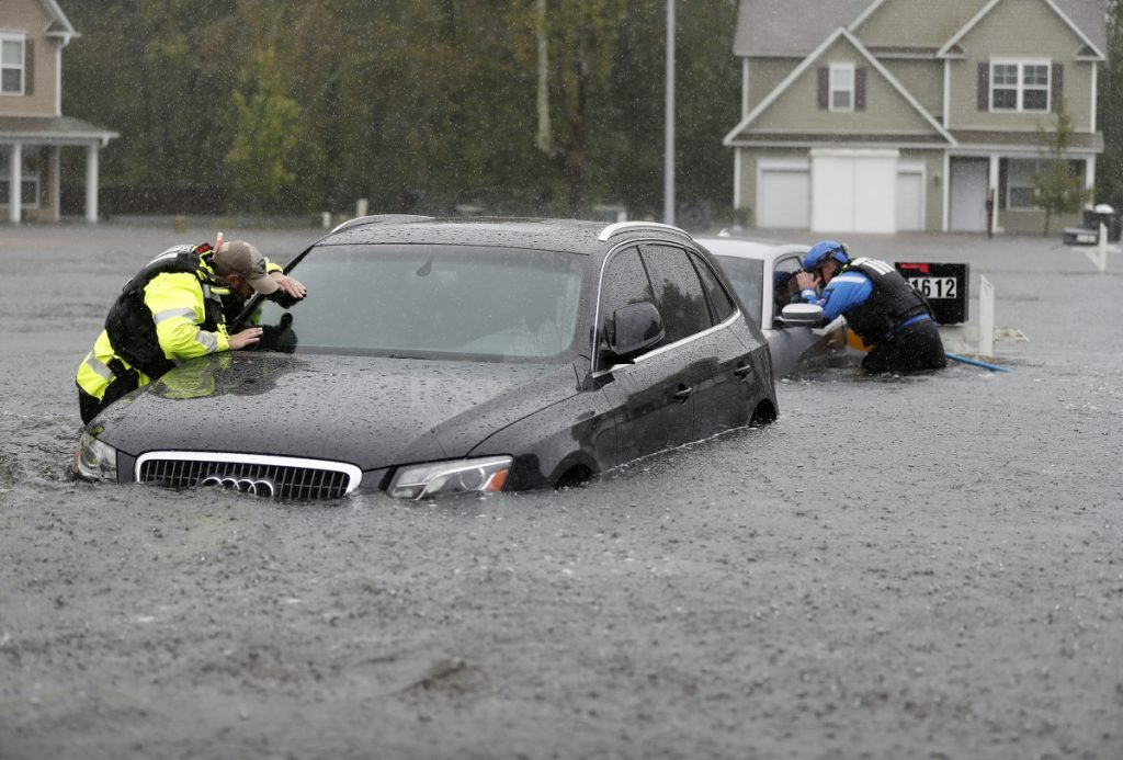 Members of the North Carolina Task Force urban search and rescue team check cars in a flooded neighborhood in Fayetteville, N.C., on Sunday, looking for residents as Florence continued to dump more than 30 inches of rain in spots.