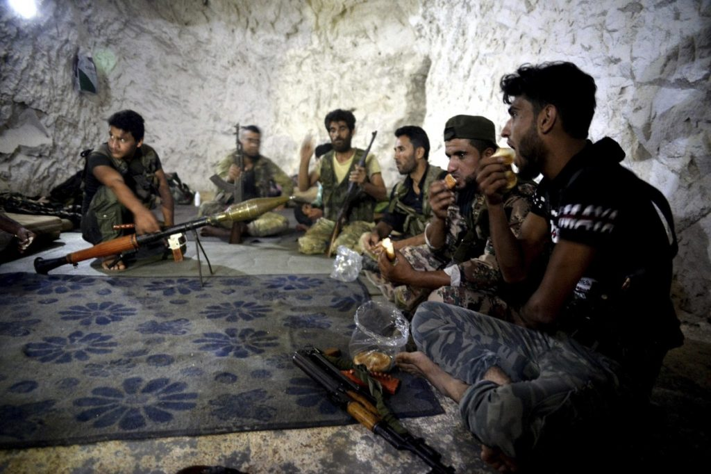 Fighters with the Free Syrian Army eat in a cave where they live near the city of Idlib, Syria, last Sunday. Tens of thousands of opposition fighters await a decisive battle with government troops backed by Russia and Iran.