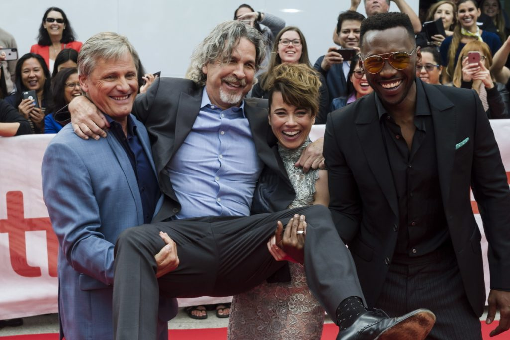"Director Peter Farrelly is lifted up by actors, from left, Viggo Mortensen, Linda Cardellini and Mahershala Ali as they arrive for the screening last week of ""Green Book"" at the Toronto International Film Festival."