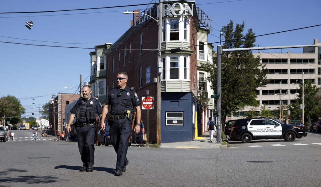 Officer Mark Keller, left, and community policing officer David Argitis cross the intersection of Alder, Oxford and Portland streets Friday. Police have expanded their presence in Bayside, the site of frequent crime and a flashpoint for discussions on the city's shelter system.