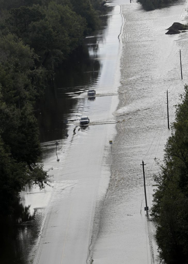Cars make their way down a road overtopped by rushing floodwater from Hurricane Florence in Dillon, S.C., on Monday. Navigation apps like Waze are trying to help motorists avoid hurricane flooding, but local authorities say people shouldn't rely on them.