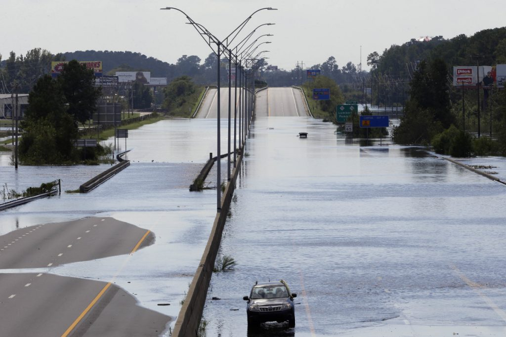 Flooded vehicles sit on a closed section of Interstate 95 in Lumberton, N.C., where the Lumber River overflowed following flooding from Hurricane Florence on Monday. Navigation apps like Waze are trying to help motorists avoid hurricane flooding, but local authorities say people shouldn't rely on them.