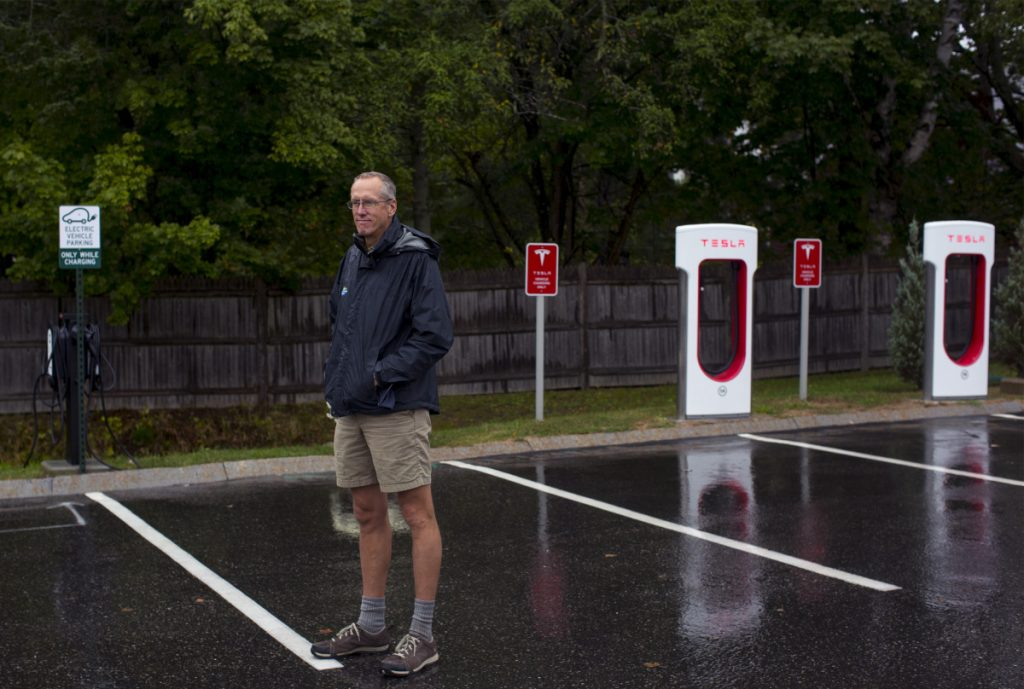 """Bill Yeo, L.L. Bean Outdoor Discovery School's retail manager, poses for a portrait in front of the store's new electric car charging stations. Yeo said if electric vehicles take off he """"hopes the whole parking lot will someday be an EV charging station."""""""