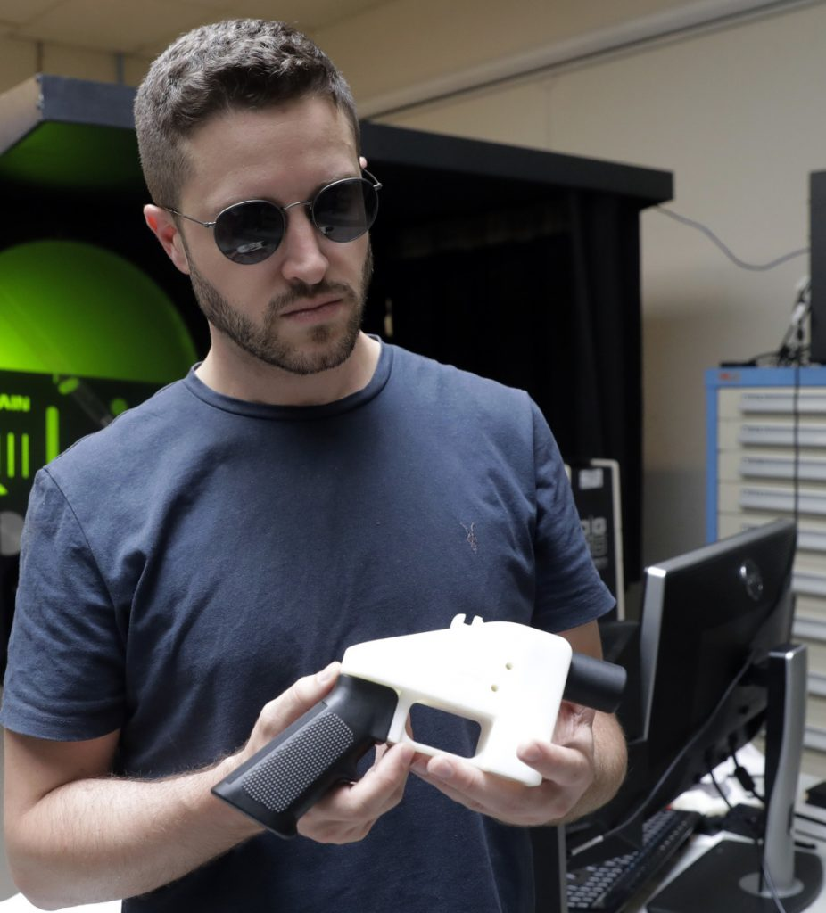 Cody Wilson, with Defense Distributed, holds a 3D-printed gun at his shop in Austin, Texas. A federal court barred him from posting the gun blueprints online.