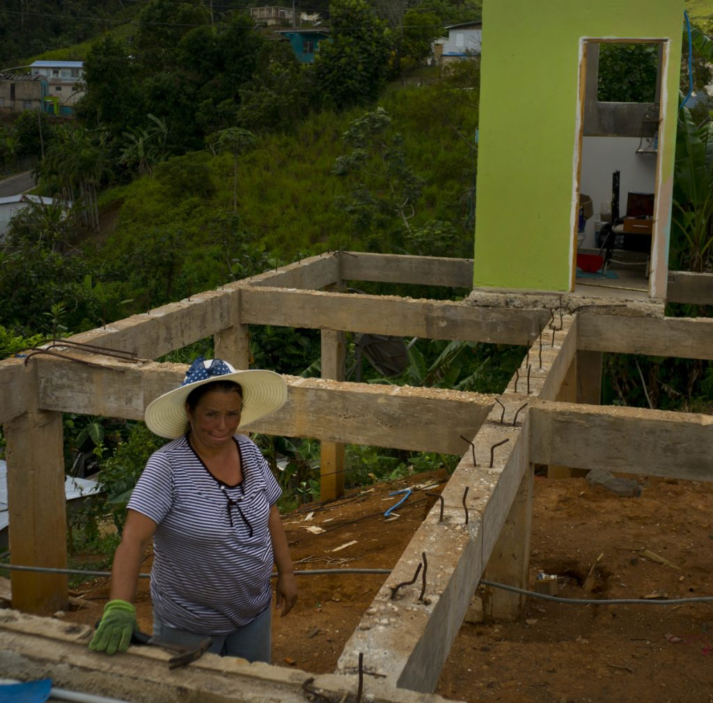 Alma Morales Rosario poses between the beams of her home being rebuilt after it was destroyed by Hurricane Maria one year ago in the San Lorenzo neighborhood of Morovis, Puerto Rico. Associated Press/Ramon Espinosa
